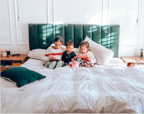 family sitting on the bed with magnesium oil spray